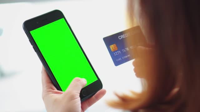 vidéos et rushes de femme shopping sur smartphone avec carte de crédit, écran vert - achat avec la carte de crédit