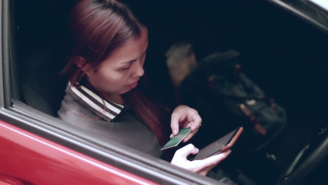 Woman Shopping Online With Smartphone And Credit Card From Red Car
