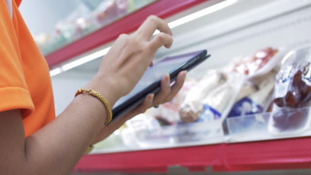 woman shopping with check list on digital tablet - frigorifero video stock e b–roll