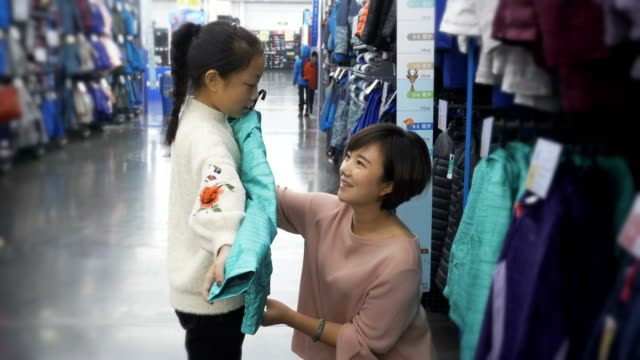woman shopping with daughter in shopping mall - warm clothing stock videos & royalty-free footage