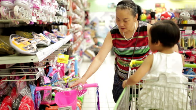woman shopping with her granddaughter in supermarket /xi'an, shaanxi, china - großeltern stock-videos und b-roll-filmmaterial