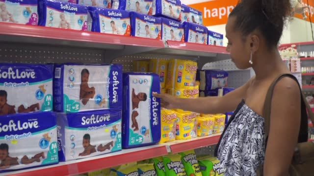 a woman shops for nappies in a store in vanuatu after the pacific nation announced plans to ban disposable diapers in a move it says will... - disposable stock videos and b-roll footage