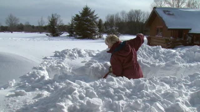 vídeos de stock e filmes b-roll de ms woman shoveling snow in front of log cabin, tweed, ontario, canada - pá para neve