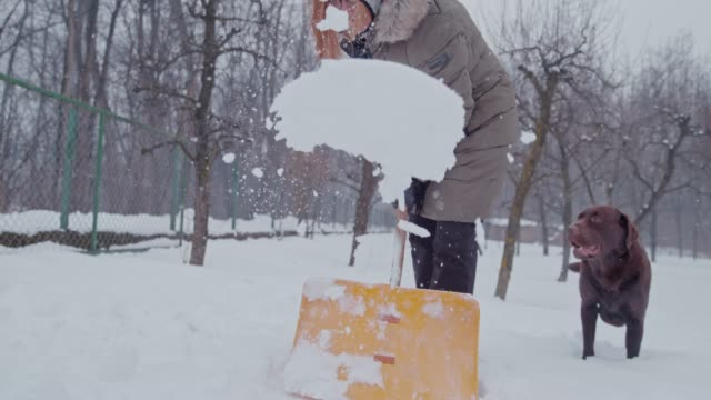 SLO MO Woman shovelling the snow