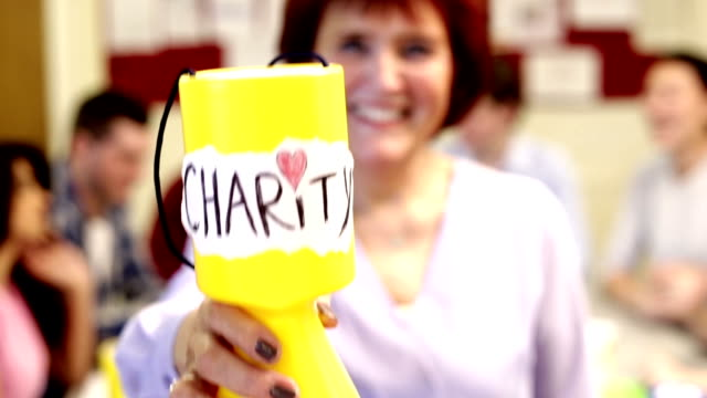 Woman Showing A Charity Money Pot To The Camera