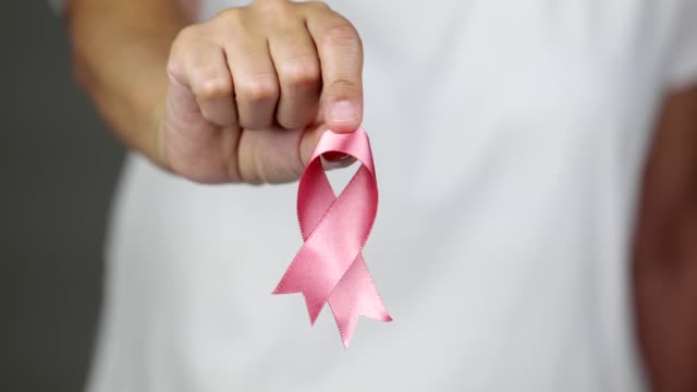 woman showing a pink breast cancer awareness ribbon towards the camera - breast cancer stock videos & royalty-free footage