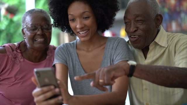 woman showing cellphone to senior couple, people smiling and having fun - brazilian ethnicity stock videos & royalty-free footage