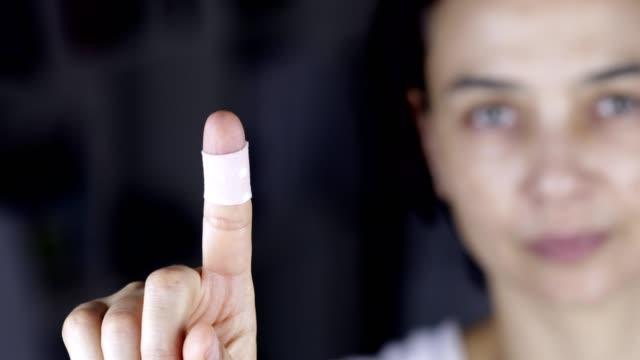 包帯、パッチで指を示す女性 - 絆創膏点の映像素材/bロール