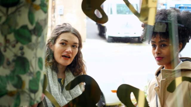 ms woman showing friend dress in window of boutique - schaufenster stock-videos und b-roll-filmmaterial