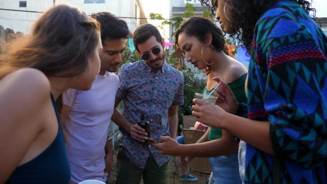 ms woman showing friends photos on smart phone during party in backyard on summer afternoon - generation z stock videos & royalty-free footage