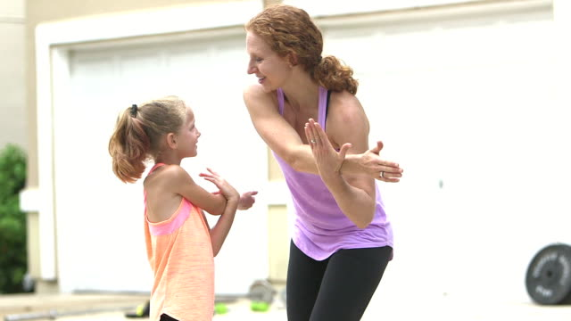 Woman showing girl how to stretch arms