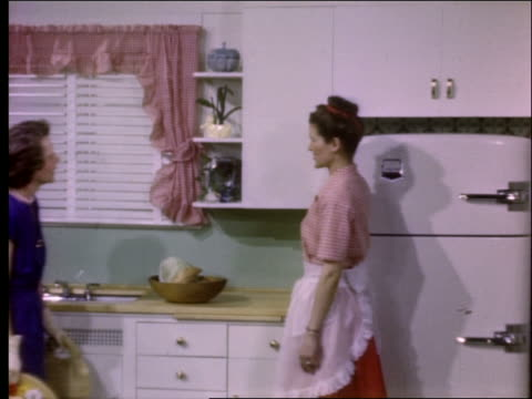 woman showing kitchen cabinets and drawer to other woman / 1950's - other stock videos & royalty-free footage
