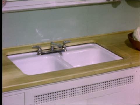 vídeos de stock e filmes b-roll de woman showing kitchen sink and cabinet to other woman / 1950's - lava loiças