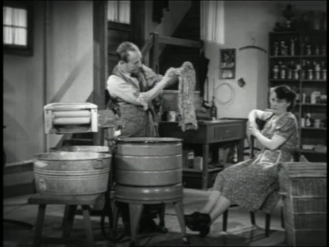 B/W 1941 woman showing man how to wash clothing with early washing machine