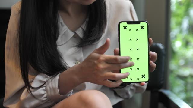 女性を示す緑の携帯電話画面 - 引きずる点の映像素材/bロール
