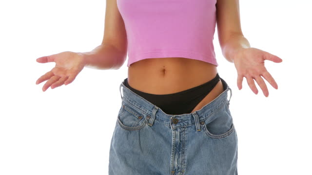 woman showing off weight loss in baggy jeans - baggy jeans stock videos & royalty-free footage