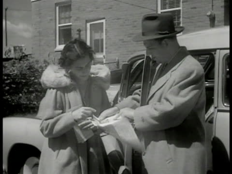 vídeos de stock e filmes b-roll de woman showing pamphlet to man by car. women at shop window, shop owner putting 'better schools' sign in window. poster through window 'better schools... - filme documentário