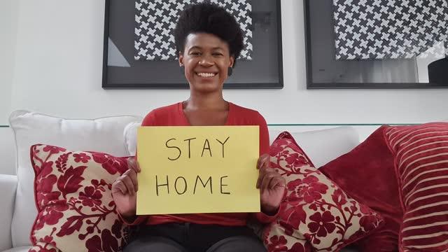 vídeos de stock, filmes e b-roll de mulher mostrando papel com 'stay home' escrito durante uma chamada de vídeo - ponto de vista da webcam - equipamento de mídia