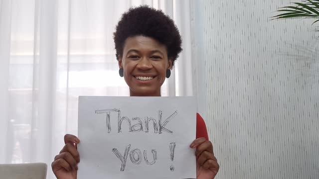 vídeos y material grabado en eventos de stock de mujer mostrando papel con 'gracias' escrito durante una videollamada - punto de vista de la cámara web - trabajador de primera línea