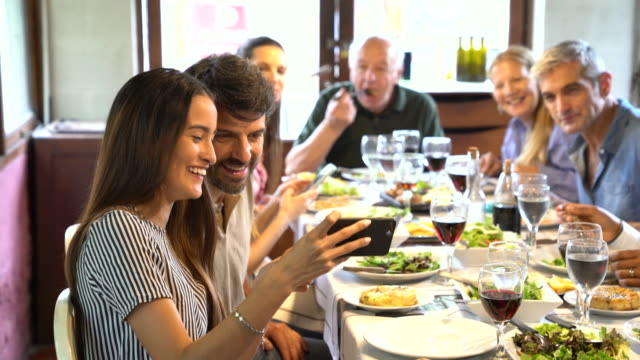 woman showing pictures on phone while family lunch at restaurant - large group of people stock videos & royalty-free footage