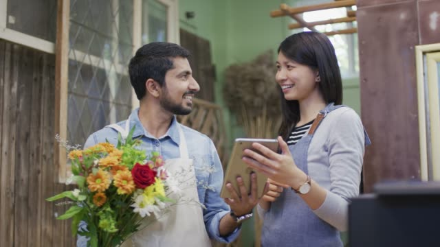 woman showing tablet to ethnic male owner of a flower shop - fioraio negozio video stock e b–roll