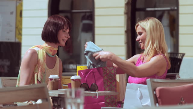 TU Woman showing what she bought to her friend over coffee