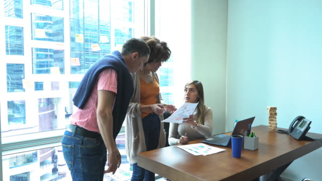 woman shows a graph to her coworkers - colombian ethnicity stock videos & royalty-free footage