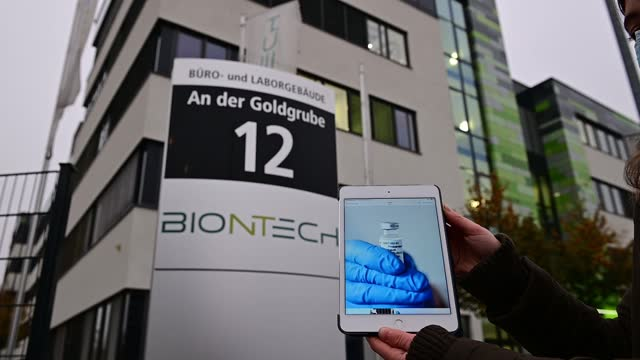 woman shows an ipad with the pictures of the covid-19 vaccine of biontech in front of the headquarters of german immunotherapy company biontech on... - big tech stock videos & royalty-free footage