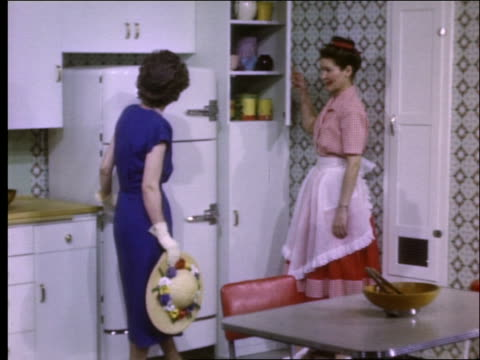 woman shows kitchen cabinets, ironing board to other woman / 1950's - bügelbrett stock-videos und b-roll-filmmaterial