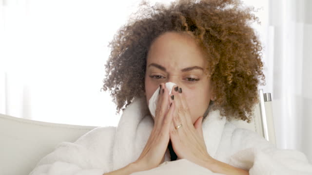 Woman sick in bed coughing and blowing nose