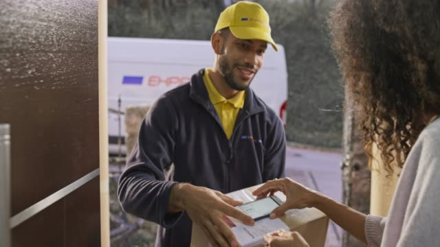 笑顔の男性宅配便によって彼女の玄関に配達されるパッケージのために署名する女性 - 配達員点の映像素材/bロール