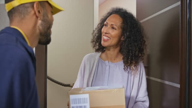 woman signing for the package delivery at the front door of her house - receiving stock videos & royalty-free footage