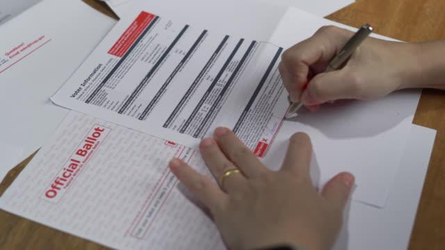 kvinna som undertecknar sin amerikanska frånvarande valsedel hemma - autograf bildbanksvideor och videomaterial från bakom kulisserna