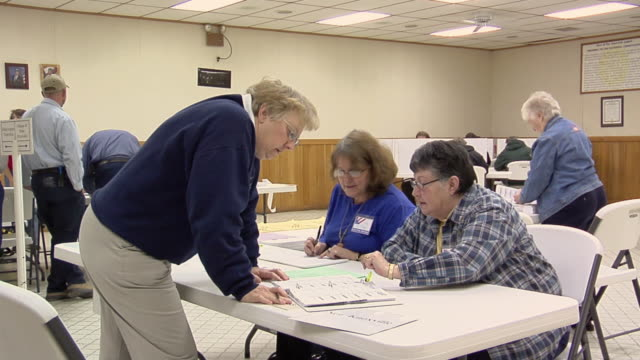 vidéos et rushes de ms, zi, woman signing in at registration table at polling place, new knoxville, ohio, usa - voter