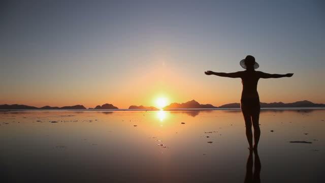 vídeos y material grabado en eventos de stock de mujer de silueta alzar los brazos en la playa al atardecer - exotismo