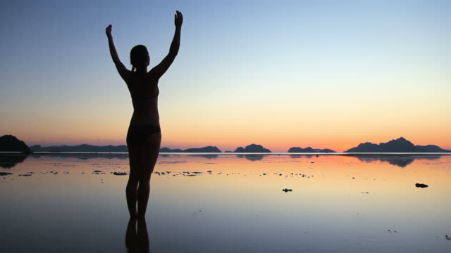 woman silhouette arms raised on beach at twilight - sun salutation stock videos and b-roll footage