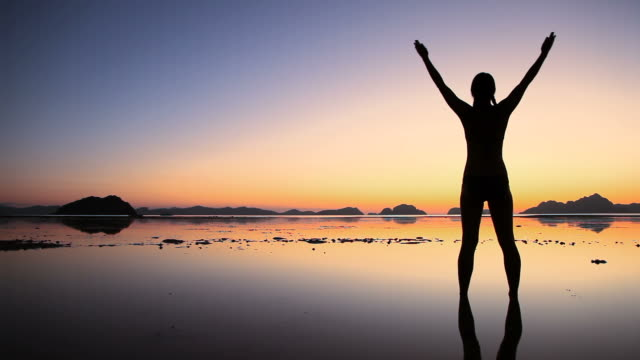 Woman silhouette arms raised on beach at twilight