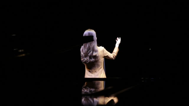 A woman singing a song in front of a microphone on the stage from the back