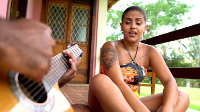 vídeos de stock, filmes e b-roll de mulher cantando e homem tocando violão - latino americano