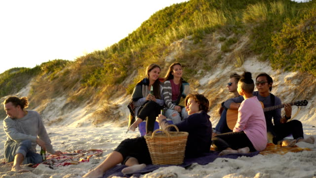 Woman singing while relaxing with friends at beach