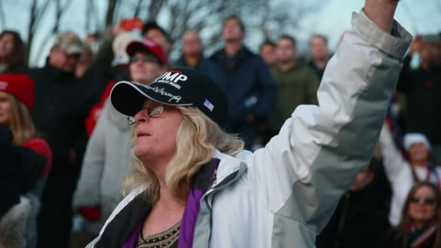 a woman sings along and waves a trump flag as lee greenwood sings god bless the usa while trump supporters gather at the lincoln memorial for the... - amtseinführung stock-videos und b-roll-filmmaterial