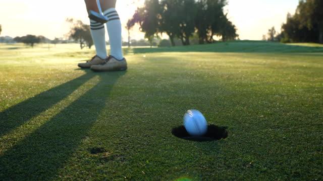 vídeos de stock, filmes e b-roll de ms woman sinking putt during early morning round of golf - bola de golfe