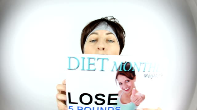 Woman Sipping Milkshake While Reading Diet Magazine