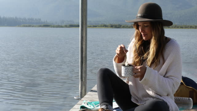 A woman sipping on coffee at the end of a dock overlooking Vermillion Lakes.
