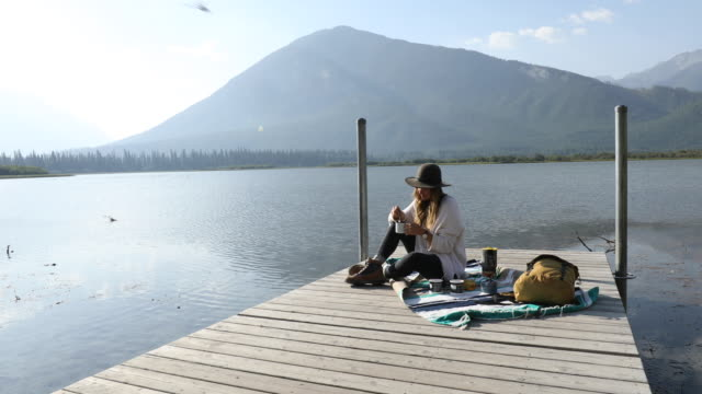 a woman sipping on coffee at the end of a dock overlooking vermillion lakes. - pier stock videos & royalty-free footage