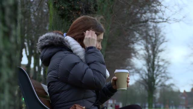 woman sips hot coffee on a park bench laughing - オーバーコート点の映像素材/bロール