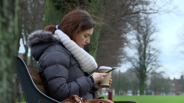 woman sips hot coffee on a park bench using her phone - cappotto invernale video stock e b–roll