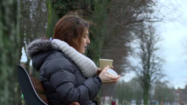 woman sips hot coffee on a park bench - オーバーコート点の映像素材/bロール