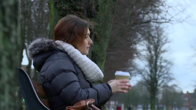 vidéos et rushes de woman sips hot coffee on a park bench waiting for someone - banc public