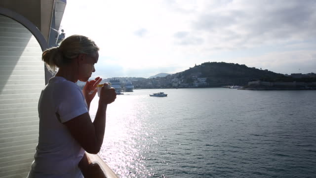 Woman sips tea while watching boat enter port, Kusadasi, Turkey